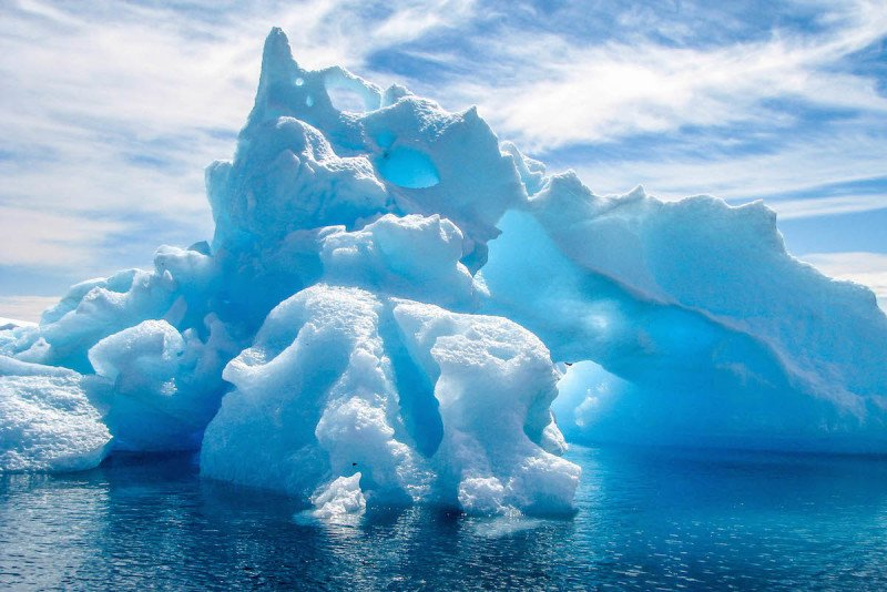 Iceberg floating next to a cruise ship in Antarctica.