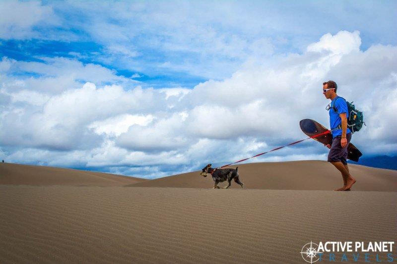 Outdoor adventure, travel, sand dunes, sand boarding, sandboarding, Great Sand Dunes, National Park, Colorado, Hiking, Kai, Desert, Dog, Miniature Schnauzer